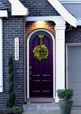 A purple front door painted in deep, dark eggplant looks dark and mysterious.
