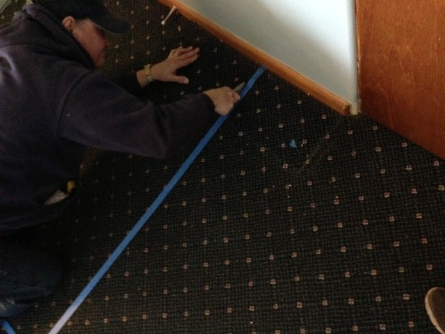 cut the carpet along a straight line with a sharp razor blade.