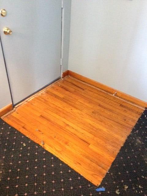 removing carpet to reveal hardwood flooring.