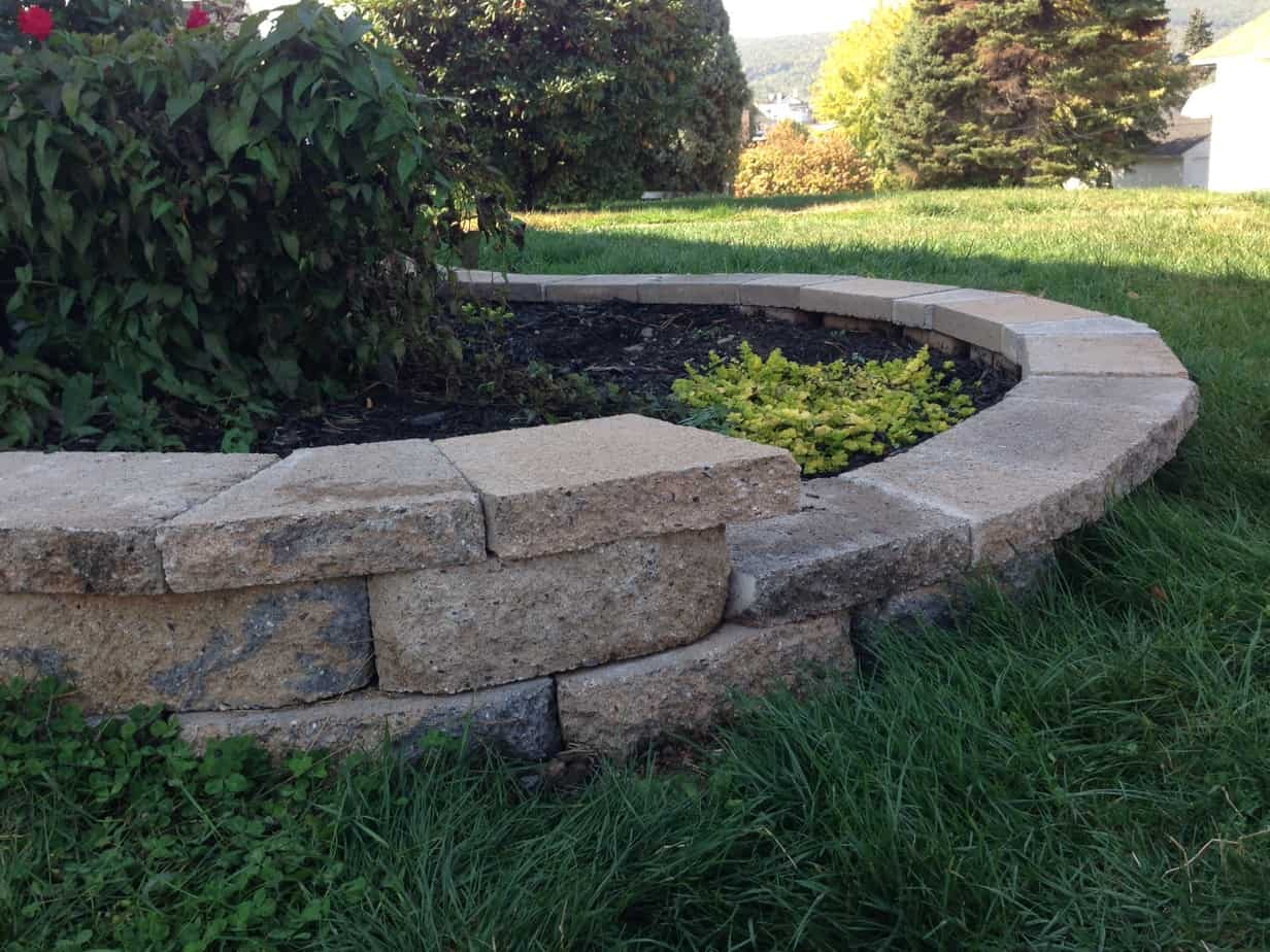 Cut stone caps for a curved retaining wall pretty purple for Curved garden wall ideas