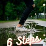 womans legs, wearing black pants and sneakers jumping in a puddle.