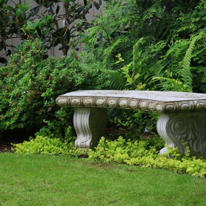 stone bench nestled into a lush garden