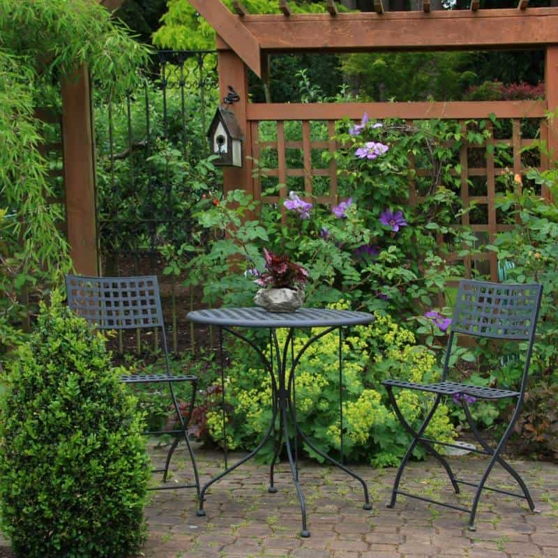 bistro table and chairs in a garden under a wooden arbor
