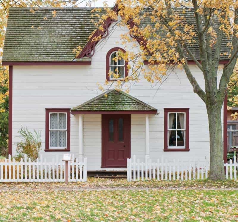 Cape code style home with red trim and low picket fence