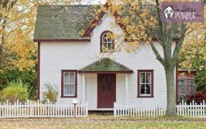 Cape Code style house with red trim and low white picket fence