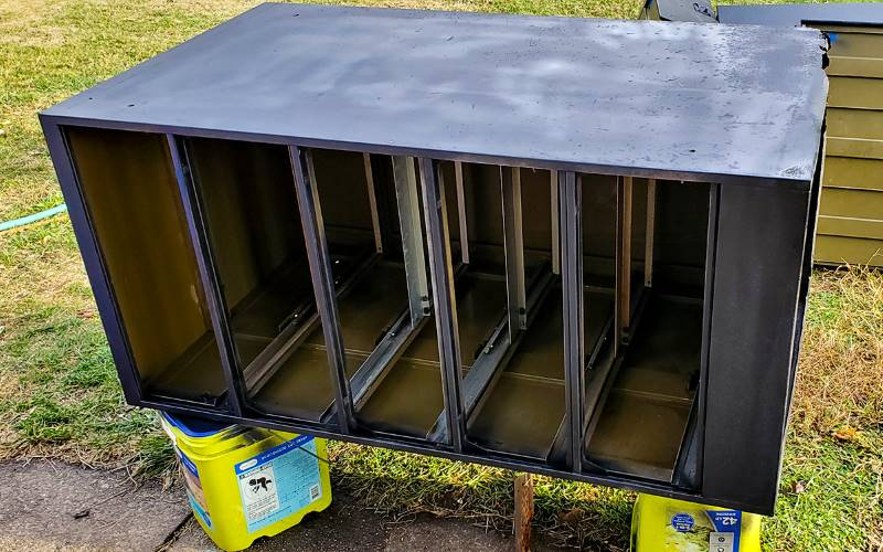Filing cabinet on its side after first coat of rust primer (black)