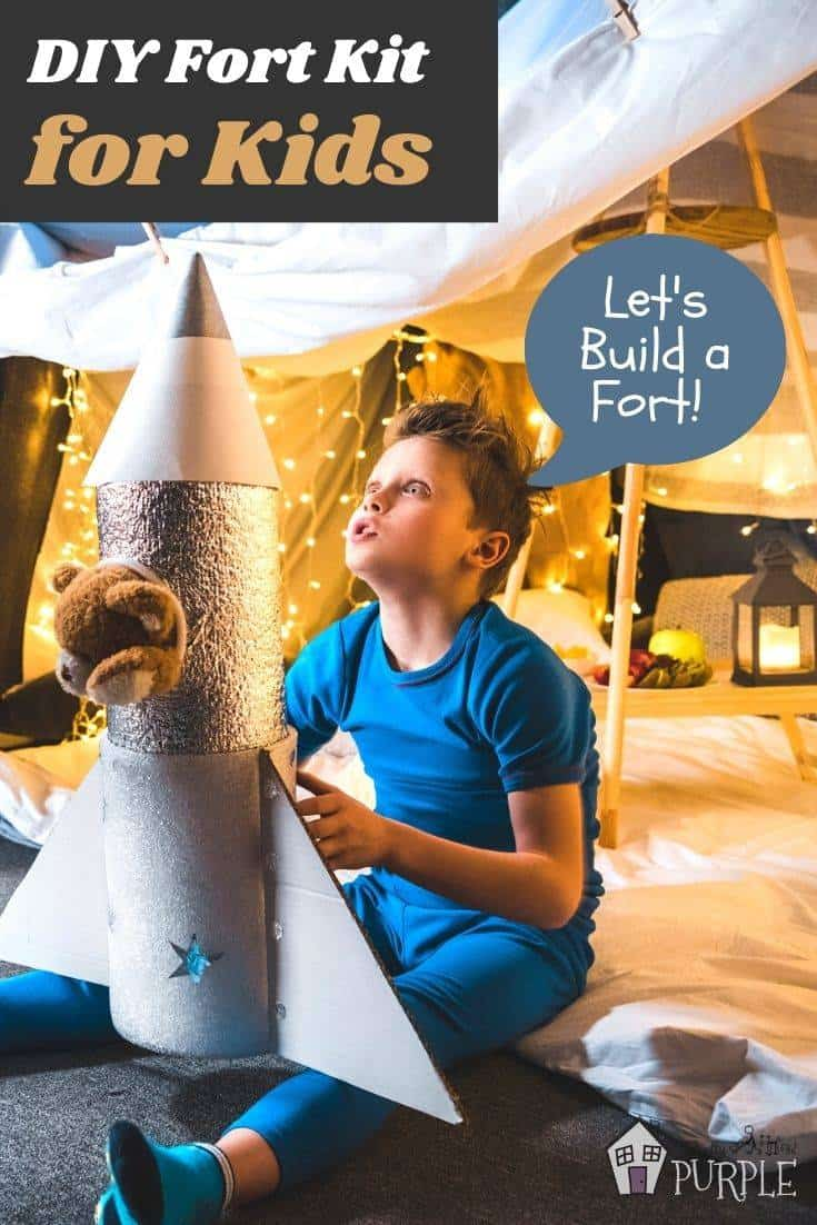 Boy in pajamas playing with rocket in blanket fort