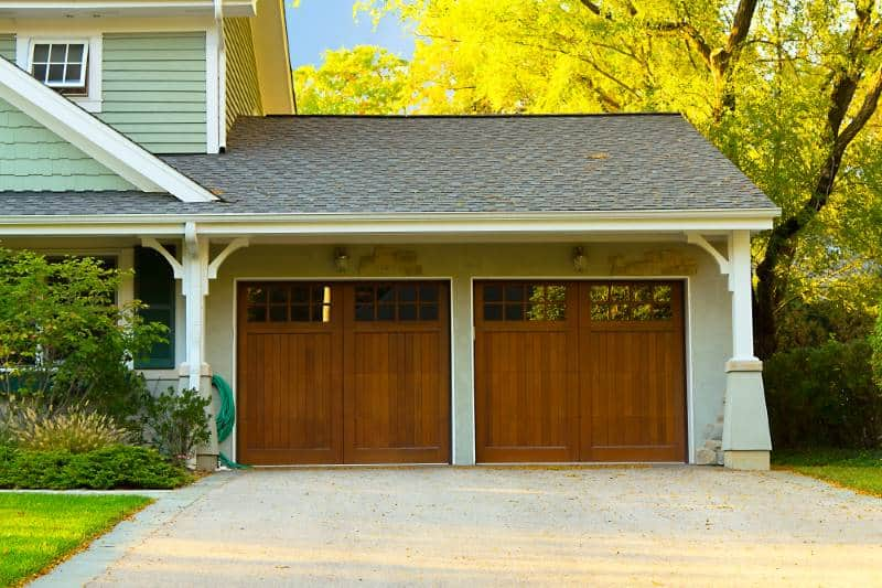 Wood garage doors attached to green home