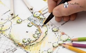 hand holding pencil drawing a garden plan layout