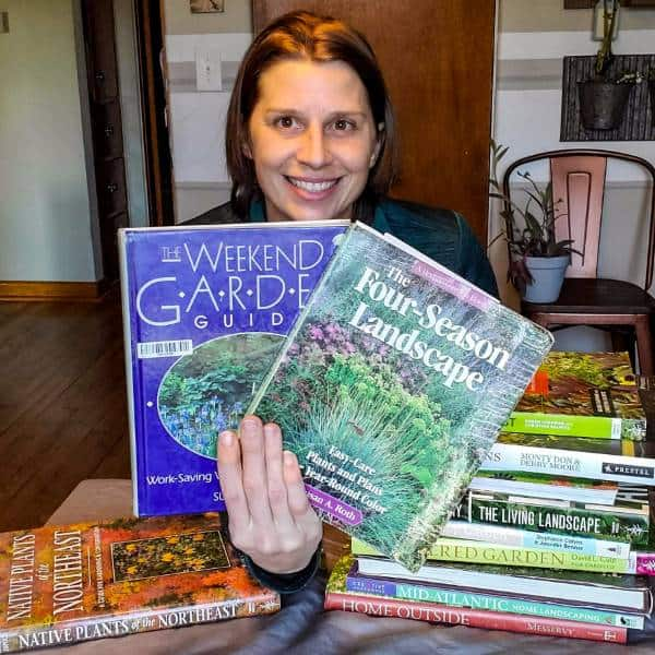 Amy holding two gardening books by Susan Roth