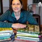 Amy learning on stacks of gardening books