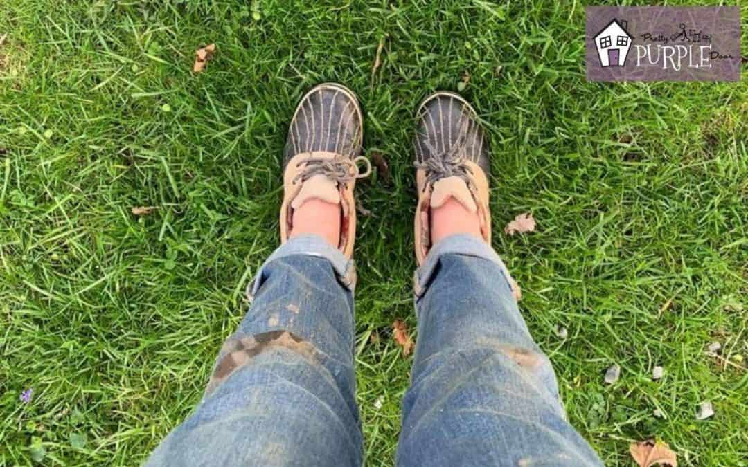 woman standing in grass with muddy pants wearing rubber garden shoes