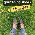 woman standing in grass taking photo downward with muddy pants and duck style gardening shoes