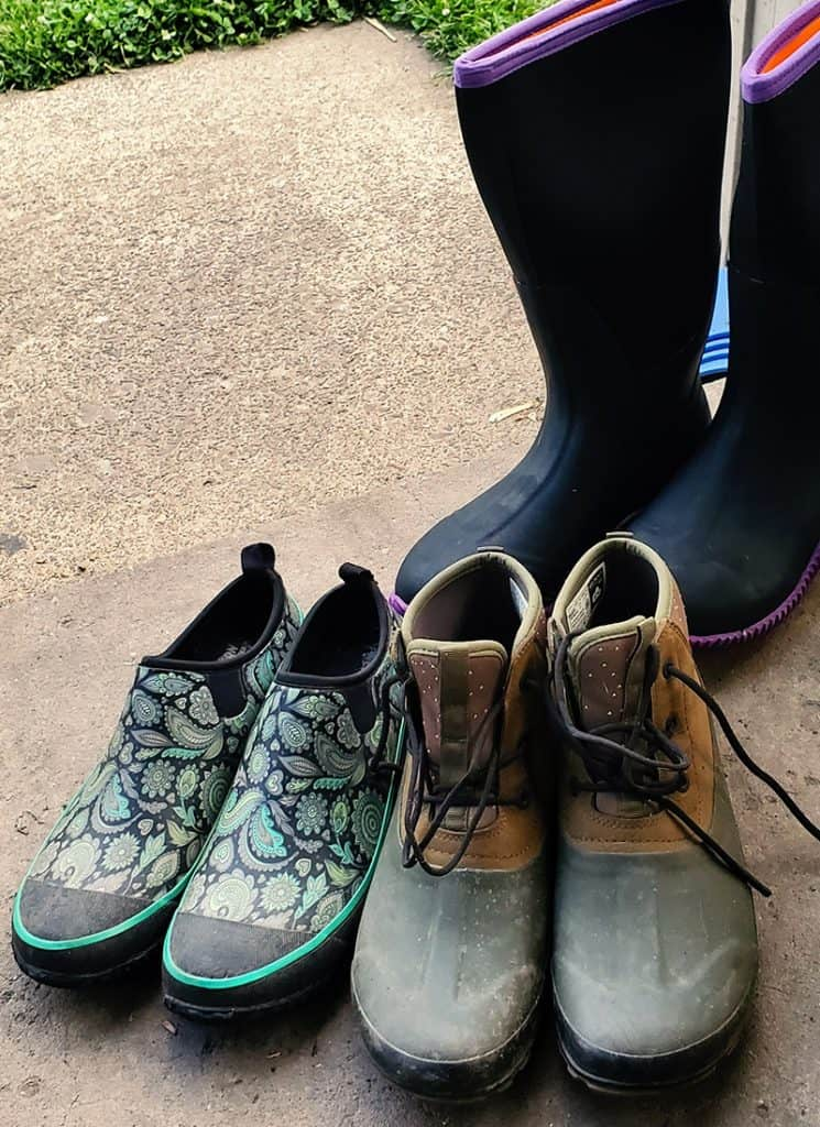 Three pairs of women's gardening shoes on porch stoop.