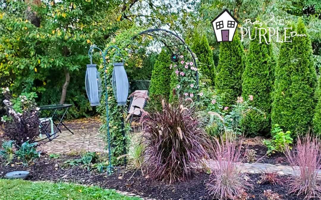 backyard garden with stone path, flowering arbor and reclaimed brick patio