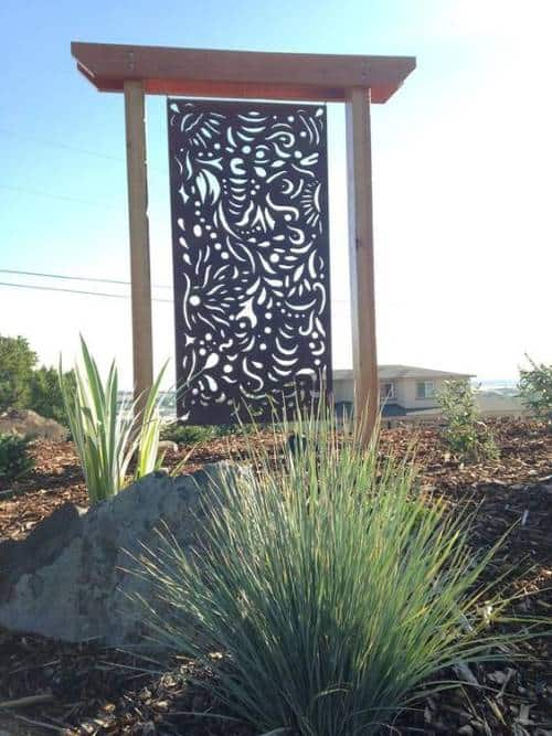Decorative metal screen on raised posts to create privacy from neighbors