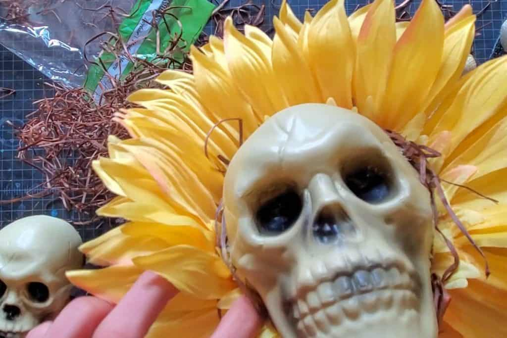 gluing raffia around the edges of the skull head that's on the sunflower face.