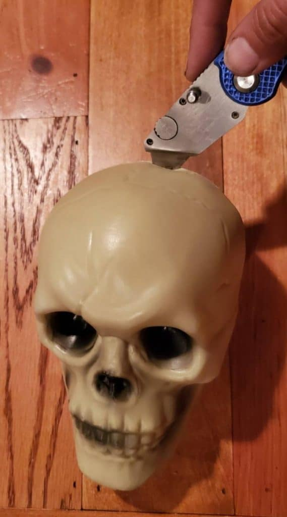 holding razorblade against plastic skull to remove the back